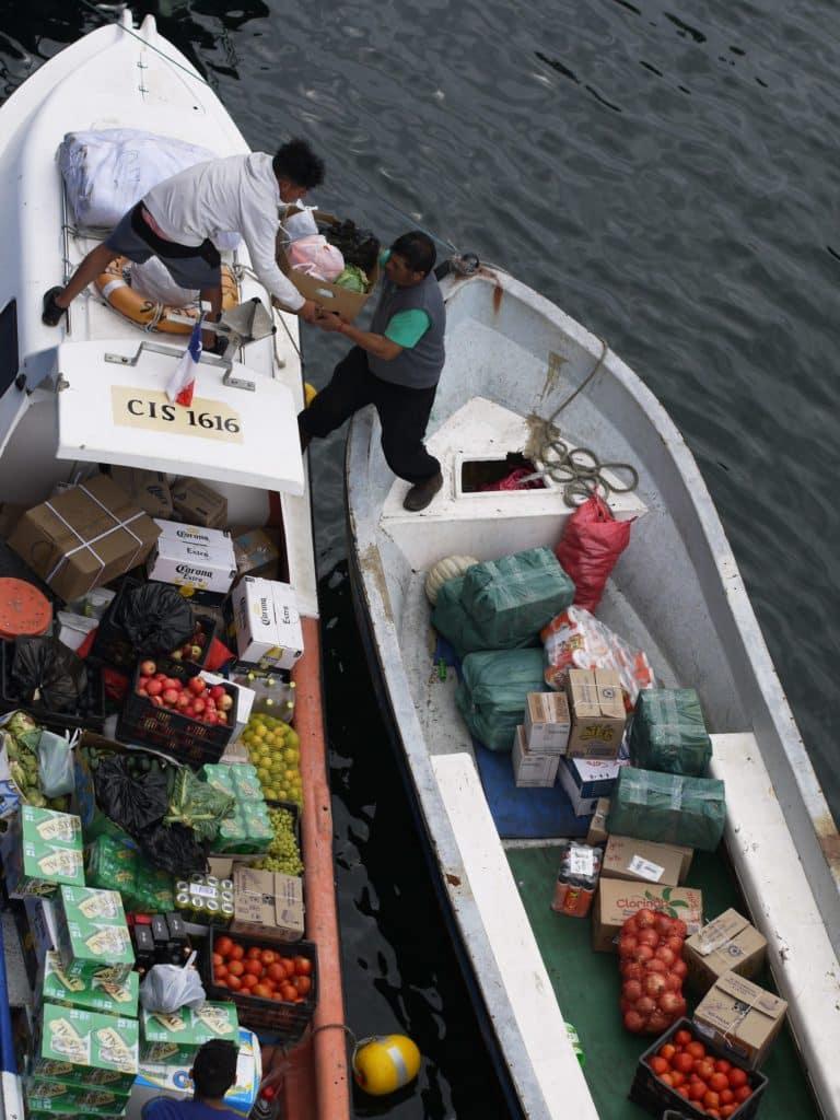 2 hommes transportant des marchandises par bateau dans le port de Valparaiso