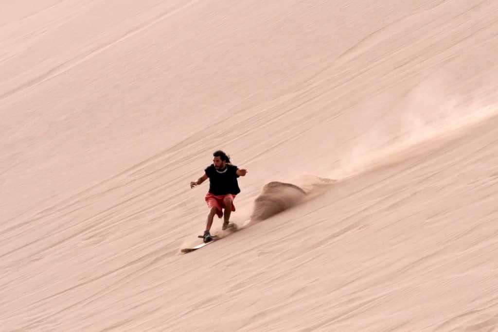 Sandboarding dans la vallée de la mort, en haut d une dune descendre sur le sable en surf board ski